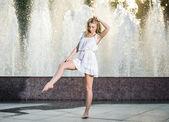 Atraktivní dívka v bílých krátkých šatech sedí před fontánou v nejžhavější letní den. dívka s šaty částečně vlhké, tanec. krásné blonďaté ženy u fontány v pozici balet