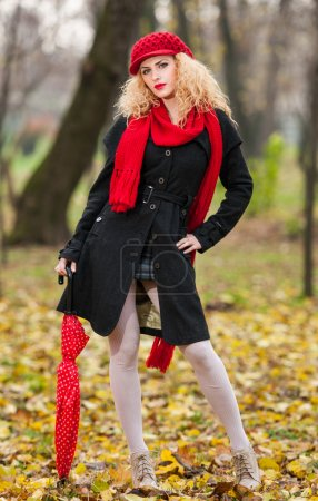 Attractive young woman in a autumn fashion shoot. Beautiful fashionable young girl with red umbrella , red cap and red scarf in the park