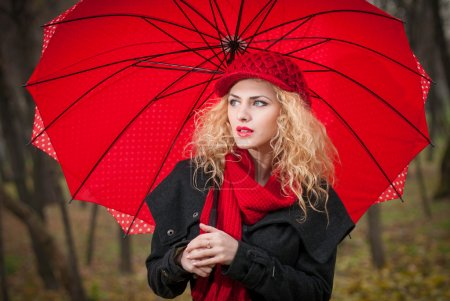Attractive young woman in a autumn fashion shoot. Beautiful fashionable young girl with red umbrella, red cap and red scarf in the park.