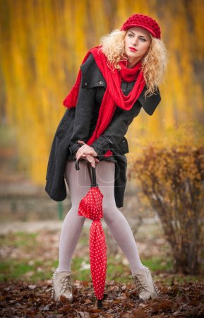 Attractive young woman in a autumn fashion shoot. Beautiful fashionable young girl with red umbrella, red cap and red scarf in the park. Blonde women with red accessories posing outdoor