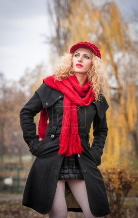 Attractive young woman in a autumn fashion shoot. Beautiful fashionable young girl with red cap and red scarf in the park. Blonde women with red accessories posing outdoor. Nice fair hair girl