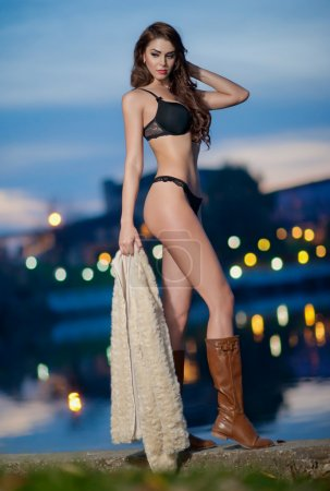 Beautiful brunette woman in black sensual lingerie posing provocatively outdoor with city lights in background. Young model wearing long leather boots in sunset. Caucasian model with long legs