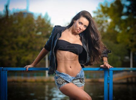 Sexy brunette in denim shorts posing provocatively outdoor. Portrait of a beautiful sexy woman with denim shorts in a park. Attractive female brunette woman posing in blue jeans shorts near a river.