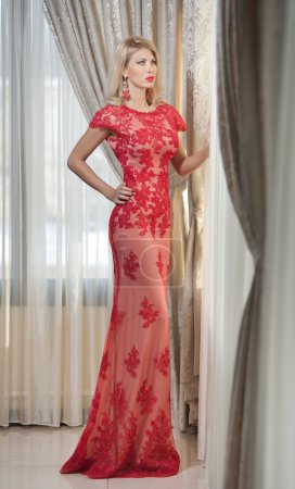 Young beautiful luxurious woman in long elegant dress. Beautiful young blonde woman in red dress with curtains in background. Seductive blonde woman with red lace dress in luxury manor, vintage style