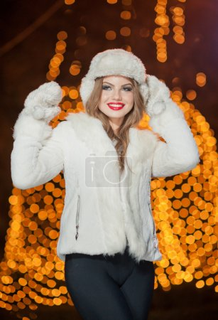 Fashionable lady wearing white fur accessories outdoor with bright Xmas lights in background. Portrait of young beautiful woman in winter style. Bright picture of beautiful blonde woman with make up