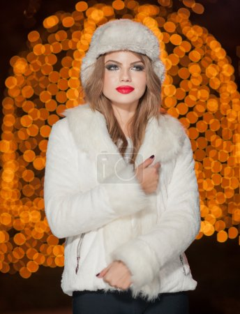 Fashionable lady wearing white fur cap and coat outdoor with bright Xmas lights in background. Portrait of young beautiful woman in winter style. Bright picture of beautiful blonde woman with make up