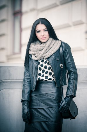 Attractive young woman in a winter fashion shot. Beautiful fashionable young girl in black leather outfit posing outdoor. Elegant long hair brunette with handbag and scarf in urban scenery.