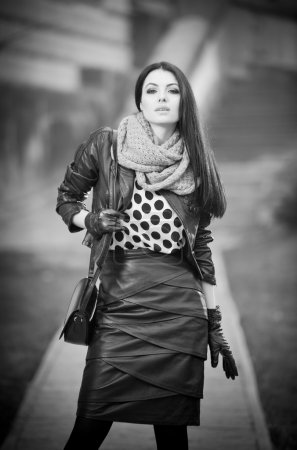 Attractive young woman in a winter fashion shot. Beautiful fashionable young girl in black leather outfit posing on avenue. Elegant long hair brunette with handbag and scarf in urban scenery.