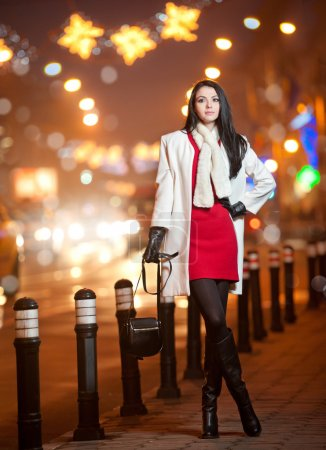 Fashionable lady wearing red dress and white coat outdoor in urban scenery with city lights in background. Full length portrait of young beautiful elegant woman posing in winter style. Street shot.