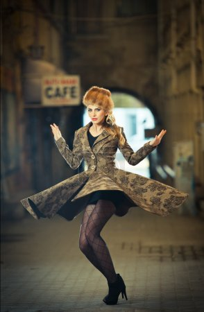 Attractive elegant blonde young woman wearing an outfit with Russian influence in urban fashion shot. Beautiful fashionable young girl with long legs and fur cap posing spinning on street