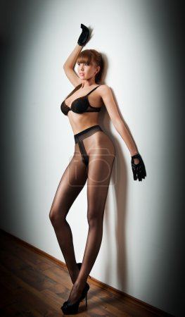 Attractive red hair model with pantyhose and black...
