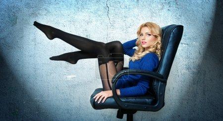 Photo pour Attrayante femme blonde sexy avec une blouse bleue vif et bas noirs pose souriant assis sur la chaise de bureau. Portrait de femme sensuelle cheveux blonds avec longues jambes sur bleu - studio tourné - image libre de droit