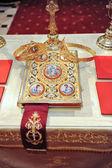 Kříže, kroužky a korun zlata na stole v kostele. Svatební oslava