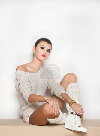 Attractive brunette model with white blouse, long stockings and high heels standing on white background. Fashion portrait of cute girl - studio shot. Beautiful fair hair woman in white posing pretty.