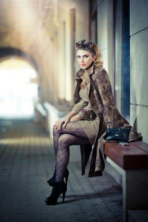 Photo pour Jolie fille blonde porte une robe courte et talons hauts - scène urbaine. mannequin avec des jambes sexy longtemps assis sur la pensée de banc. femme élégante porte costume avec influence russe pose décontractée - image libre de droit