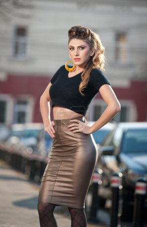 Attractive young woman in a urban fashion shot. Beautiful fashionable young girl with tight-fitting clothes and long legs posing on the street. Elegant blonde female posing in urban scenery