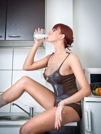 Photo pour Jolie femme sexy en lingerie, boire du lait dans la cuisine. Portrait d'une fille sensuelle avec longues jambes, porter des vêtements confortables douillettes dans une cuisine moderne tenant un verre de lait. tir intérieur. - image libre de droit