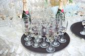 Svatební výzdoba, sklenice na víno a šampaňské flétny na stole. Dekorace s lahví a sklenic šampaňského na sváteční stůl. Luxusní svatební dekorace na stůl v restauraci. Elegantní událost