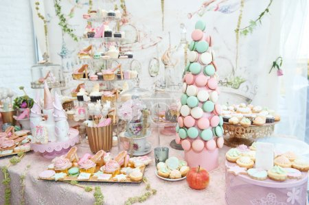 Photo for Wedding decoration with pastel colored cupcakes, meringues, muffins and macarons. Elegant and luxurious event arrangement with colorful macaroons. Wedding dessert with macaroons - Royalty Free Image