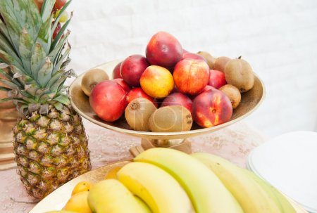 Photo for Fruits arrangement. Fresh various fruits elegant decoration. Assortment of exotic fruits. Multicolored fruits. Wedding decoration with fruits on restaurant table, pineapple, bananas, nectarines, kiwi - Royalty Free Image