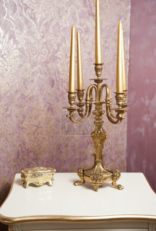 Golden candlestick with five candles on white table, in front of luxurious textured wall. Vintage candelabra, candles and golden boxy on table with wallpaper as background