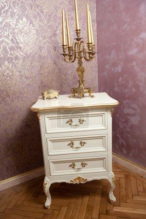 Photo pour Bougeoir doré avec cinq bougies sur des meubles en bois blanc devant un mur texturé luxueux. Bougeoir vintage, bougies et boîte dorée sur commode classique avec fond d'écran - image libre de droit