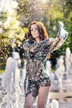 Attractive girl in black transparent veil playing with water in a summer hottest day. Wet girl enjoying fountains. Young beautiful happy female playing with outdoor water fountains in sunny day.
