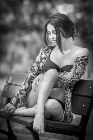 Attractive girl in swimsuit sitting relaxed on a bench. Fashionable female model with romantic look posing in park. Beautiful woman in bikini with nice legs sitting daydreaming, black and white.