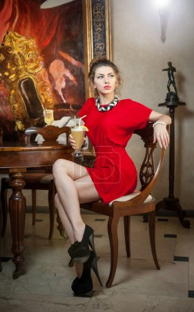 Fashionable attractive young woman in red dress sitting in restaurant. Beautiful lady posing in elegant vintage scenery with a coffee latte glass. Attractive girl on high heels in luxurious interior