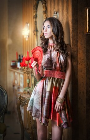 Young beautiful brunette woman in elegant multicolored dress standing near a large wall mirror. Sensual romantic lady holding a red fan in luxurious vintage interior, daydreaming. Pretty girl with fan