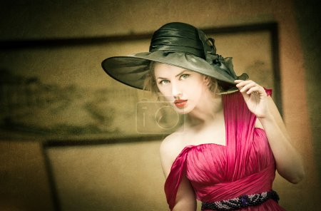 Charming blonde woman with black hat, retro image. Young beautiful fair hair female posing vintage. Mysterious lady with movie star look. Attractive fashionable girl looking as an American actress