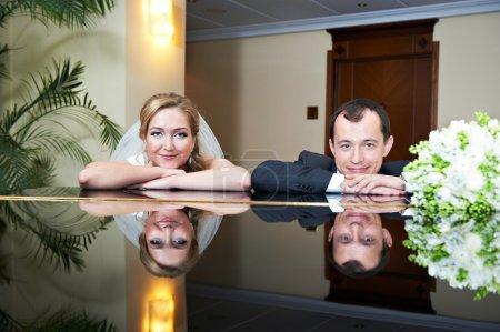 Happy bride and groom in interior of hotel