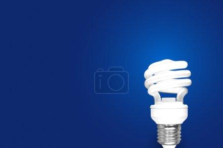 Foto de Compact Fluorescent Bulb on blue background (CFL) - Imagen libre de derechos