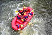 Skupina mužů a žen rafting na divoké vodě