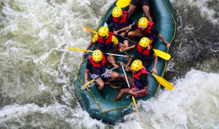 A group of men and women white water rafting