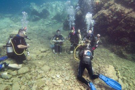 Photo pour Groupe de jeunes hommes et une femme apprenant à plonger - image libre de droit