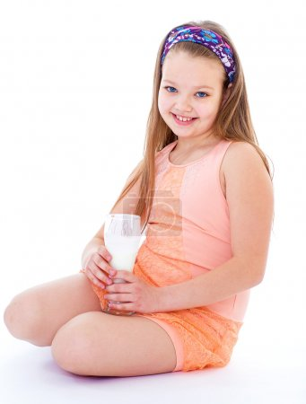Charming little girl with a glass of milk.