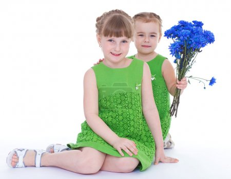 Two beautiful little girl with a beautiful bouquet of blue flowe