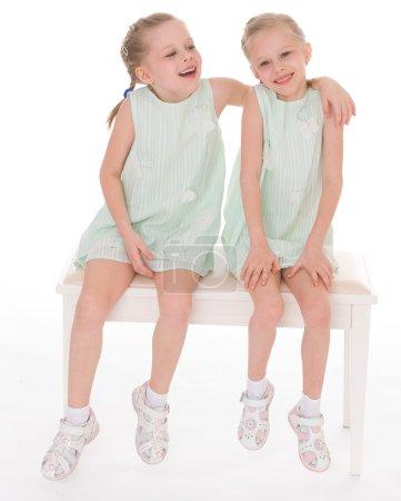 Cute sisters having fun sitting on a chair.