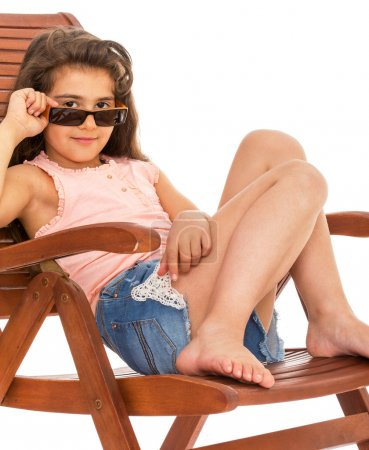 Photo for Barefoot girl in jeans shorts sitting on a wooden deck chair on white background - Royalty Free Image
