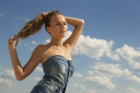 Beautiful girl draw back her hair into a ponytail