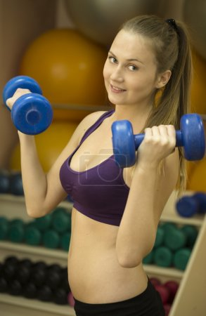 Beautiful fitness woman practicing with dumbbells