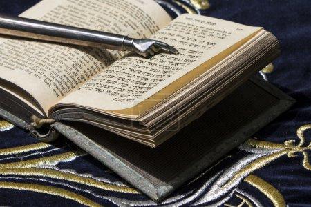 Photo pour Livre de bible ouvert en hébreu avec bâton pointant vers l'argent sur un tissu sombre avec couronne dessus - image libre de droit