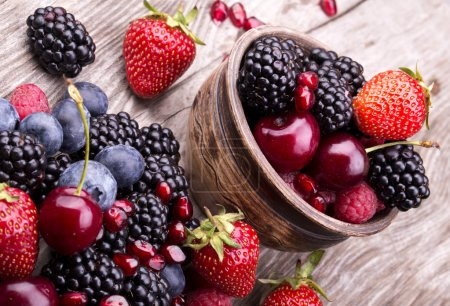 Photo pour Fruits d'été délicieux sur une table en bois. cerise, baies bleues, fraises, framboises, mûres, Grenade - image libre de droit