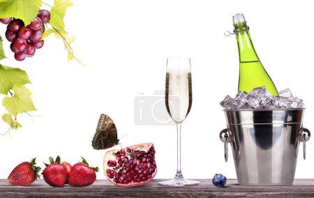 Photo pour Fraise, raisin, berrie bleue, grenade et seau à glace avec bouteille de champagne et verre sur une table isolée sur un fond blanc - image libre de droit