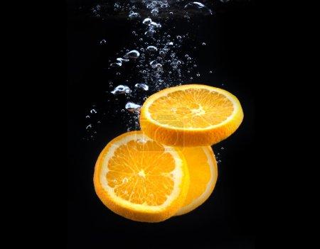 Photo pour Tranche d'orange dans l'eau avec des bulles, sur fond noir - image libre de droit