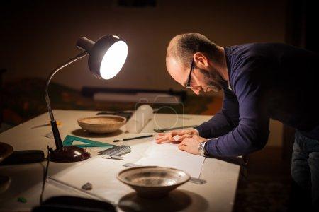 Photo pour Un archéologue examinant certains pots anciens sur un bureau - image libre de droit