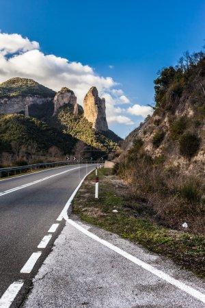 Photo pour Une route à voie unique faisant une courbe avec un pic nu sur le fond - image libre de droit