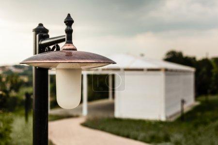 Photo pour Une lampe ornementale dans une arrière-cour avec un patio dans le fond - image libre de droit