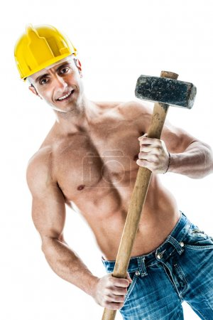Photo for A very muscular and handsome manual worker with a sludgehammer and a yellow helmet isolated over white - Royalty Free Image
